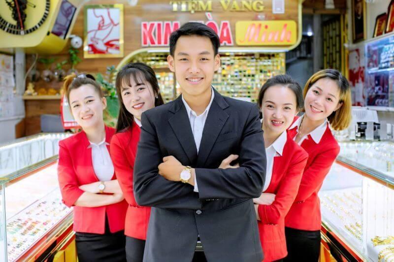 nhân viên tiệm vàng chụp ảnh tại cửa tiệm
